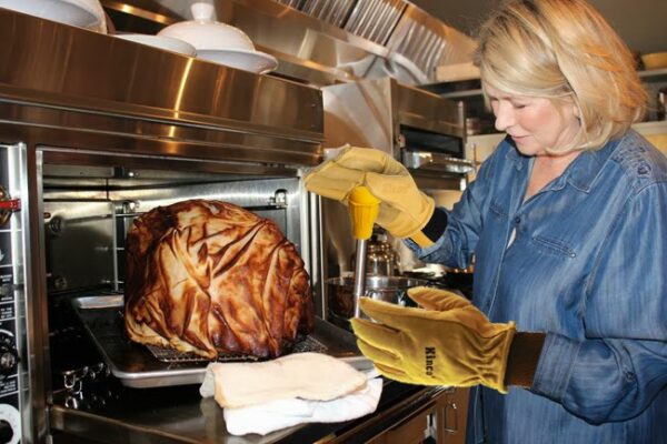 Martha Stewart removes a turkey from the overn while wearing Kinco gloves